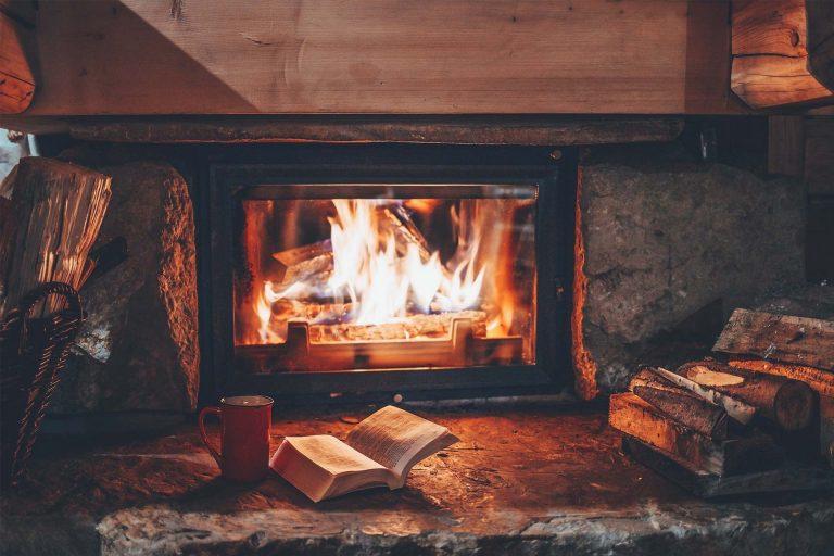 feu de cheminée avec devant un livre et une tasse